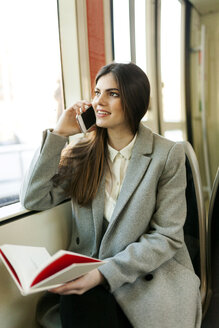 Portrait of smiling young woman on the phone in tramway - VABF01596