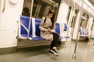 Spain, Barcelona, woman sitting in underground train using cell phone - VABF01599