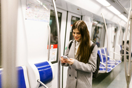 Spain, Barcelona, young woman in underground train looking at cell phone - VABF01602
