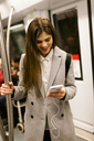 Young businesswoman using cell phone in underground train - VABF01605