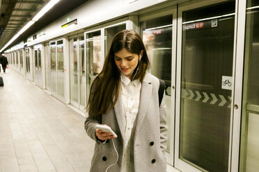 Young woman using cell phone and earphones in a passageway - VABF01608