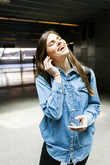 Portrait of happy young woman  listening music with cell phone and earphones - VABF01611