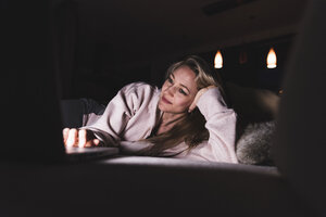 Smiling woman lying on couch at home using laptop - UUF13481