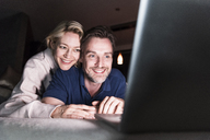 Happy couple lying on couch at home looking at laptop - UUF13484