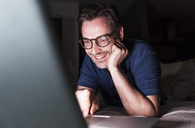 Portrait of smiling man lying on couch at home using laptop - UUF13490