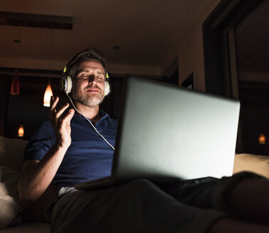 Man sitting on couch at home listening music with headphones and laptop - UUF13493