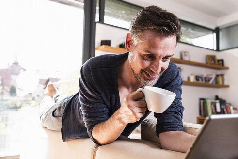 Portrait of smiling man with cup of coffee lying on backrest of couch using tablet - UUF13499