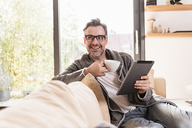 Portrait of smiling man with cup of coffee sitting on couch with tablet - UUF13502