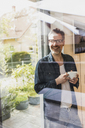 Portrait of laughing man with cup of coffee standing behind glass door at home - UUF13505