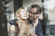 Happy mature couple behind windowpane at home - UUF13508
