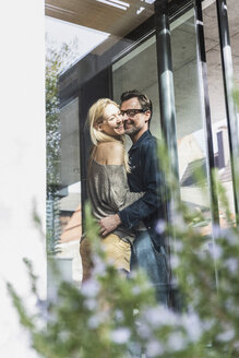 Happy mature couple standing on terrace of their house - UUF13511