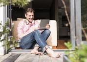 Smiling man sitting at open terrace door using laptop - UUF13526