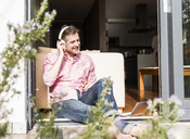 Smiling mature man sitting at open terrace door listening music with headphones - UUF13529