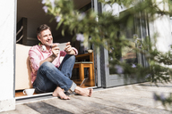 Smiling mature man with smartphone sitting at open terrace door - UUF13532