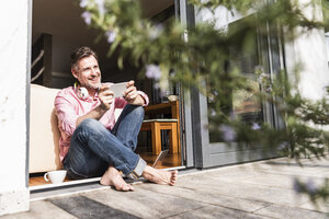 Smiling mature man with smartphone sitting at open terrace door - UUF13532