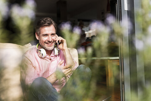 Smiling mature man on the phone sitting at open terrace door - UUF13535