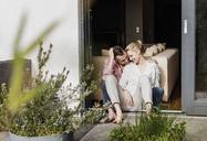 Happy mature couple relaxing together at open terrace door - UUF13544