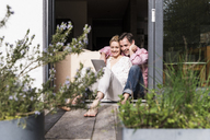 Mature couple relaxing together at open terrace door using tablet - UUF13547