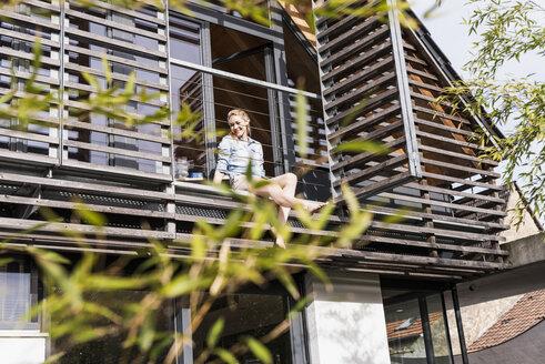 Woman relaxing on balcony of her house - UUF13553