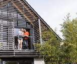 Happy mature couple standing on balcony of their house - UUF13559