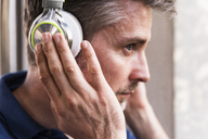 Man listening music with headphones, close-up - UUF13577