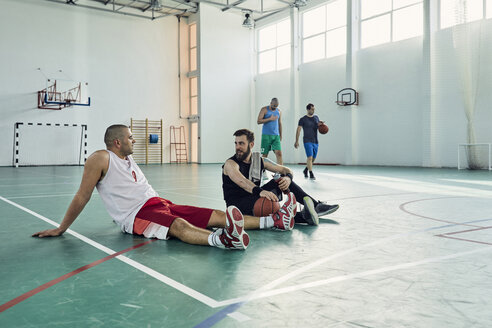 Basketball players during break, sitting on court - ZEDF01354