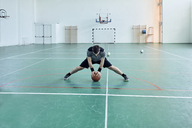 Man with basketball, stretching legs, indoor - ZEDF01381