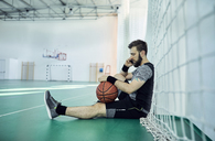 Man with basketball using smartphone, indoor - ZEDF01384