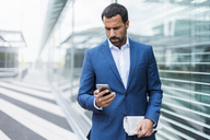 Portrait of businessman using smartphone - DIGF04182