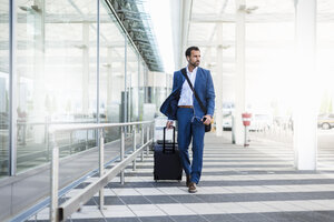 Businessman with trolley and smartphone at airport - DIGF04188