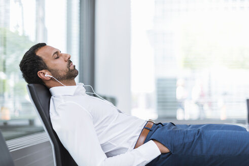 Businessman with earphones, closed eyes - DIGF04212