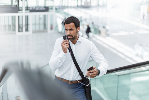Businessman using smartphone, earphones, on escalator - DIGF04218