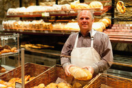 Smiling baker holding loaf of bread - CUF01179