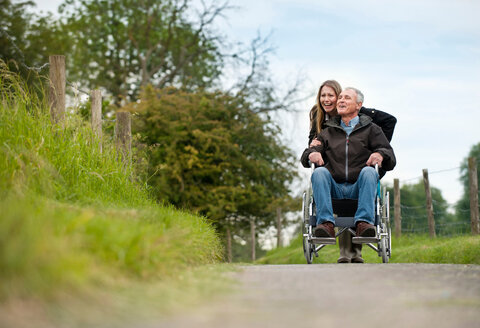 Woman pushing father in wheelchair - CUF01239