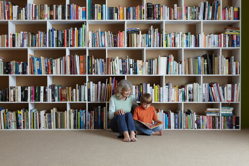 Woman reading with grandson by bookshelf - CUF01261