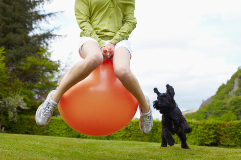 Woman on bouncy ball playing with dog - CUF01282