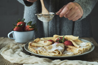 Woman preparing pancakes with strawberries for breakfast - BZF00389