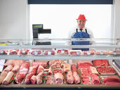 Butcher standing behind meat counter - CUF01781
