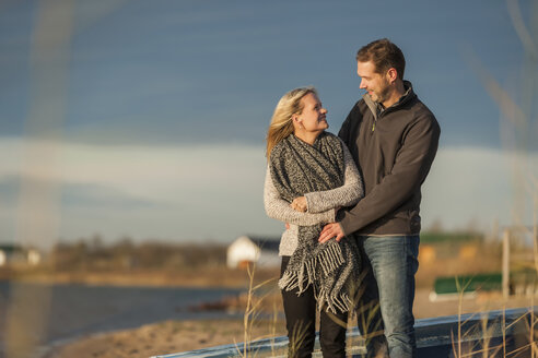 Happy couple standing at lake shore, embracing - PAF01834