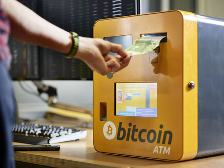 Hand inserting 100 Euro note into bitcoin ATM - CV00450
