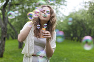 Young woman blowing bubbles - ISF00365