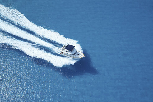 Motor yacht ploughing across blue sea - ISF00464