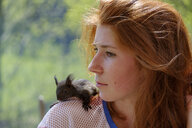 Portrait of redheaded teenage girl with squirrel on her shoulder - LBF01931