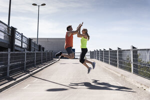 Jogging couple jumping for joy, highfiving - UUF13599