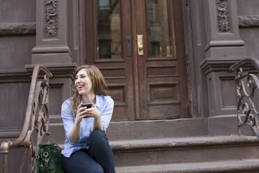 Young woman in steps of building with cellphone - ISF00754