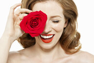 Woman covering eye with red rose - ISF00895