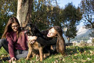 Two young women hugging dog, Calolziocorte, Lombardy, Italy - CUF01873