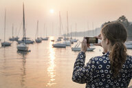 Rear view of woman photographing boats at sunset, Lazise, Veneto, Italy, Europe - CUF01888