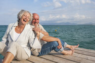 Couple hugging and laughing on jetty - CUF01933