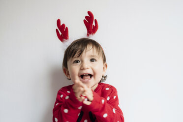 Portrait of happy baby girl with reindeer antlers headband singing and clapping hands - GEMF01938